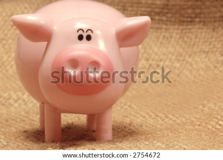 toy pig standing on a burlap background