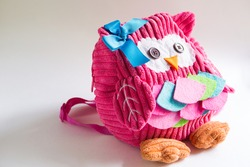 Toy pink backpack for girls in the shape of an owl with eyes buttons, applique, ribbon and embroidery. Handmade, DIY with children. Gray background