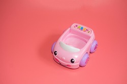 Toy pink funny car for little girls isolated on pink background. Copy space.