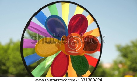 toy pinwheel multi-colored, rotated by the wind against blue sky. colored decorations for a children's party. concept of a beautiful holiday. #1331380694