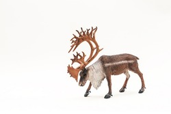 Toy plastic deer with antlers on a white background. Realistic replica of an animal