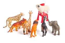 Toy plastic figurines of animals on white isolated background. One against all. Crowd of animals in front of their leader. Leadership concept. Speech to the people. Following the charismatic leader.