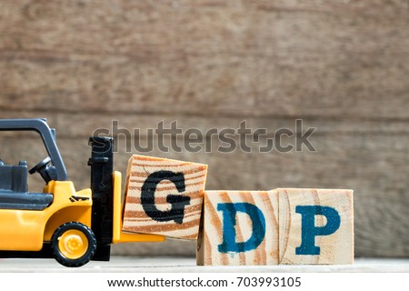 Toy plastic forklift hold block G to compose and fulfill wording GDP (Gross domestic product or Good distribution practice) on wood background #703993105