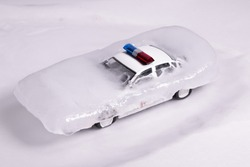 toy police car thawing from ice. frozen police car