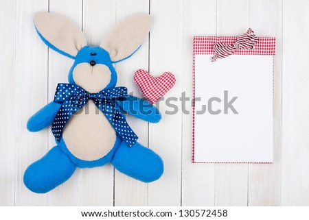 Toy rabbit, heart and notepad on white wood background