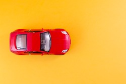 Toy red car on the yellow background top view