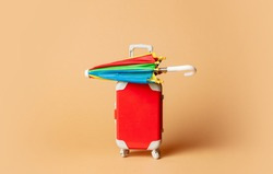 Toy red suitcase and umbrella on yellow background