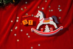 Toy rocking horse made of wood on a red background. The calendar