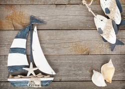 Toy sailboat and fish with seashells on a wooden background with copy space