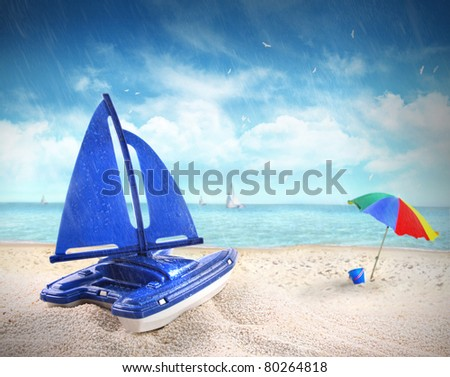 Toy sailboat in sand with beach scene in background