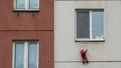 Toy Santa Claus climbing on the wall. Santa Clause figure hanging on rope from a window of house.