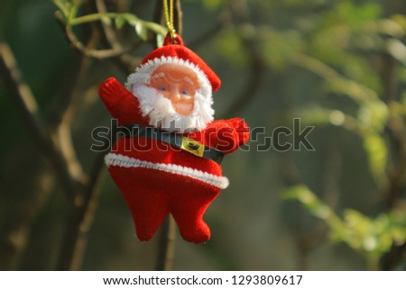 Toy Santa Claus hangs on the branches of a tree with young foliage. Spring has come. #1293809617