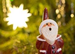 Toy santa claus smoker statue standing in front of decorated Christmas tree