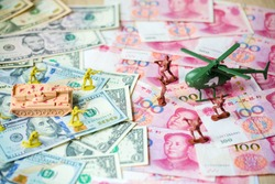 Toy set, tank, soldiers and helicopter placed on US banknotes,dollar currency pile and china banknotes, yuan currency. business and economy war. new world war from business and economy concept.