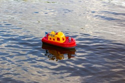 Toy ship floating on the river. A bright red and yellow plastic ship. Toy steering wheel. Children's water toys. A child's dream of sea travel. Games with children in nature.