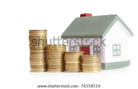 Toy small house and coins in the form of the diagram.  concept of dearness of habitation