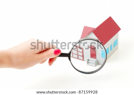 Toy small house through the magnifying glass. Closeup. Isolated.