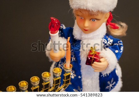 Toy Snegurochka lighting the Hanukkah candles. In December 2016 Jewish Hanukkah holiday coincides with Christmas and secular New Year.