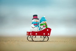 Toy snowman against tropical ocean background. Christmas in hot vacation. Warm New Year climate, theme for posters, greeting cards