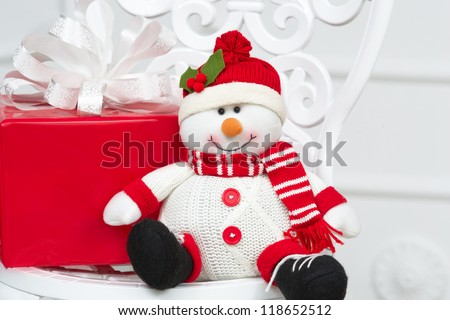 Toy snowman with red box Christmas gift sitting down on a vintage chair