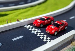 Toy sport cars on a breadboard. Two reds racing cars on race track