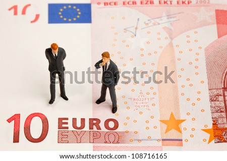 Toy train figures on a ten euro note