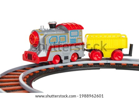 toy train with freight car trolley on railway tracks, isolated on white background, children's railway with steam locomotives, battery powered train Photo stock ©
