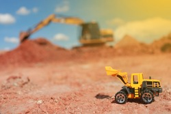 Toy Truck and Construction machinery yellow and green with Sand and Soil Pile of stones  red on rough area red And the pile of construction machinery is working construction concept environment