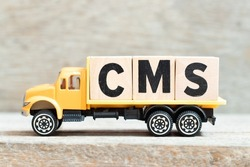 Toy truck hold alphabet letter block in word CMS (Abbreviation of Content management system) on wood background
