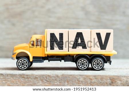Toy truck hold alphabet letter block in word NAV (Abbreviation of Net asset value) on wood background Imagine de stoc ©
