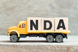 Toy truck hold alphabet letter block in word NDA (Abbreviation of Non disclosure agreement) on wood background