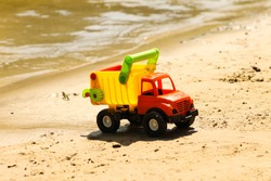 Toy truck near water on the sandy beach