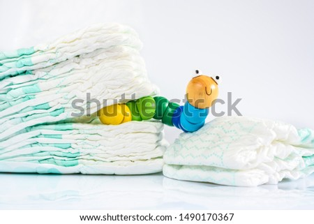 Toy worm with smile next to a pile of diapers, to illustrate concepts of health and childhood intestinal diseases. Isolated on white #1490170367