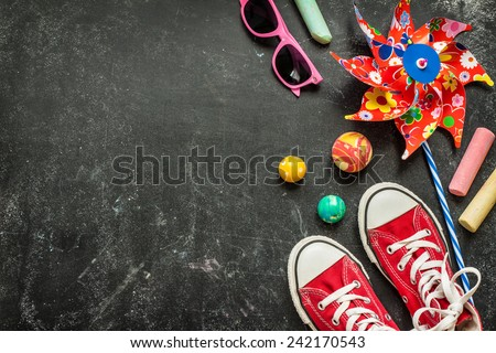 Toys and red sneakers on black chalkboard from above. Childhood - holiday or summer fun concept. Background layout with free text space.