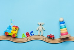 Toys background with copy space. Kids toys train, ABC letters, bear, car and pyramid on toy wooden railway on blue background with blank space for text. Top view, flat lay.