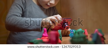 Toys crafted by hand. Role games. Boy playing with toys. Child 4 - 5 years taking picture of crafted toys. Young photographer taking picture. Animation school. Media school. Alternative education