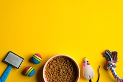 Toys for cat and bowl with dry food on yellow background. Pet care and training concept. Flat lay, top view.