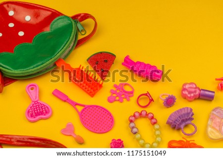 Toys for girls from a bag in the form of strawberries. children's cosmetics and jewelry Flat lay Pink toys on a yellow background. View from above. Kindergarten. #1175151049
