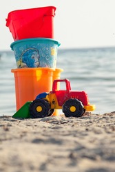 Toys for the beach for children on the sand with sea in the background. Three colorful buckets stacked and a bulldozer.