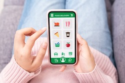 Tpo view of young asian teenage girl in concept next normal life from coronavirus impact using smart phone on hand and pay by credit card at home. Food delivery or grocery order service at home.