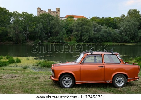Trabant car in Sarospatak, Hungary, with the ruins of Rakoczi castle in the background.