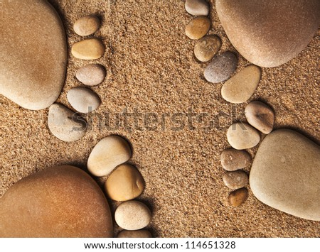 trace bare feet made of pebble stones on the beach sand texture background