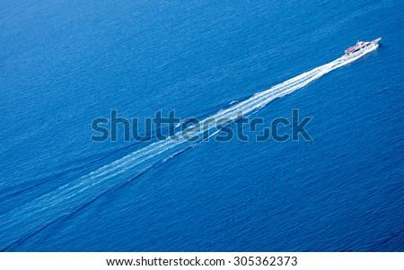 Trace from high-speed yacht over deep-blue sea surface. Ligurian sea, Italy.