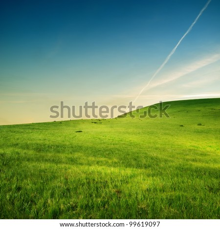 Stock Photo trace of airplane on the sky over green hills