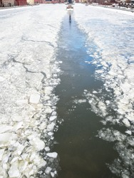 trace of excursion ship in ice of frozen Moskva river along Krymskaya and Prechistenskaya embankments in winter