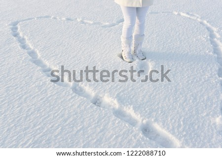 Traces in the snow made by footsteps, creating a heart symbol. Legs of anonymous woman in winter snow boots. #1222088710