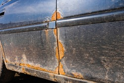 Traces of rust on the door of a dirty car