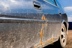 Traces of rust on the driver's door of a dirty car