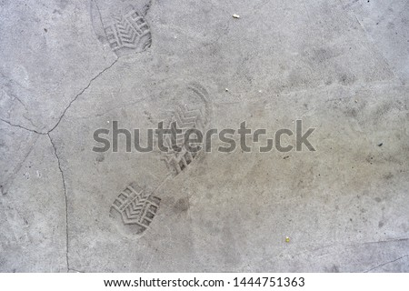 traces of shoes on the concrete floor. Imprints of shoes on the concrete floor. Shoe markings left behind in wet cement by contractor's reckless workmen. Shoe prints background #1444751363