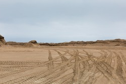 Traces of trucks on the sand in the career